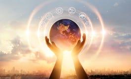 Mains abstraites de paume touchant la terre la nuit sur la ville de coucher du soleil image libre de droits