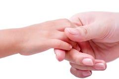 Mains adultes jugeant la main d'un enfant d'isolement sur le blanc Image libre de droits