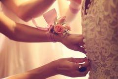 Mains aidant la jeune mariée avec la robe de mariage Photos stock