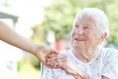 Mains aînées de fixation de femme avec le gardien Photographie stock libre de droits