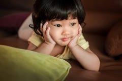 Mains asiatiques mignonnes de fille sur Chin et pose sur le sofa et le regard Outsid Images libres de droits