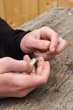 Mains attachant l'attrait de pêche Photo stock