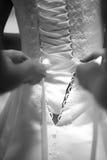 Mains attachant une robe de mariage Photos stock