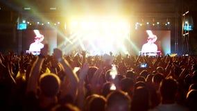 Mains augmentées à un concert de rock battant simultanément, foule des spectateurs sur l'éclat de fond de la scène, banque de vidéos