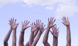 Mains augmentées en air contre le ciel Image stock