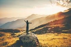 Mains augmentées par homme aux montagnes de coucher du soleil photographie stock