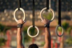 Mains aux anneaux plongeant l'homme faisant l'exercice utilisant des anneaux photos libres de droits