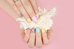 Mains avec de beaux ongles manucurés et coquille de mer Photos stock