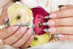 Mains avec de longs ongles manucurés français artificiels décorés du scintillement photo libre de droits