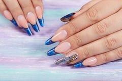 Mains avec de longs ongles manucurés français bleus artificiels photo libre de droits