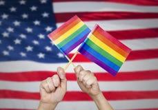 Mains avec des drapeaux d'arc-en-ciel au-dessus de fond américain Image stock