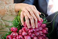 Mains avec des jeunes mariés d'anneaux sur le bouquet de mariage du rose Photographie stock