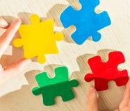 Mains avec des morceaux de puzzle Photos libres de droits