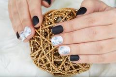Mains avec des ongles manucurés colorés avec le vernis à ongles noir et blanc photo stock
