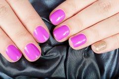Mains avec des ongles manucurés couverts de rose et de vernis à ongles d'or Photos libres de droits
