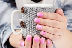 Mains avec des ongles manucurés tenant une tasse de thé avec la couverture tricotée Images libres de droits