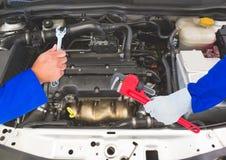 Mains avec des outils réparant une voiture Photo libre de droits