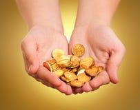 Mains avec des pièces d'or photographie stock libre de droits