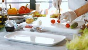Mains avec des tomates de coupe de couteau banque de vidéos