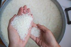 Mains avec du riz, plan rapproché comment choisir le riz ? photographie stock libre de droits