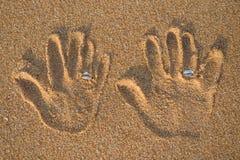 Mains avec l'anneau de mariage sur le sable Photos libres de droits