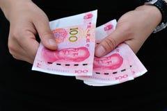Mains avec l'argent chinois de yuans Image libre de droits
