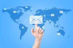 Mains avec la distribution du courrier du monde sur la carte du monde Photographie stock
