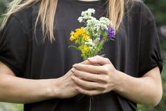 Mains avec le bouquet des fleurs photographie stock libre de droits