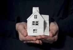 Mains avec le modèle de maison Photos stock
