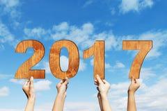 Mains avec le numéro 2017 sur le ciel Images stock