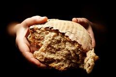 Mains avec le pain du pain déchiré Photographie stock