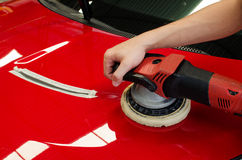 Mains avec le polisseur d'action de daul polissage sur la surface de voiture photos stock