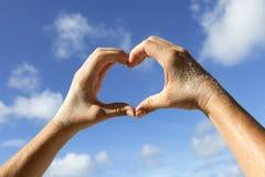 Mains avec le symbole d'amour d'exposition de sable Photo libre de droits