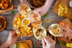 Mains avec le vin rouge grillant au-dessus de la table servie avec la nourriture Photo stock