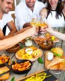 Mains avec le vin rouge grillant au-dessus de la table servie avec la nourriture Image stock