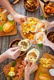 Mains avec le vin rouge grillant au-dessus de la table servie avec la nourriture Images libres de droits