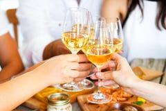 Mains avec le vin rouge grillant au-dessus de la table servie avec la nourriture Photographie stock