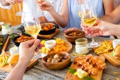 Mains avec le vin rouge grillant au-dessus de la table servie avec la nourriture Photos stock