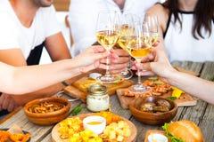 Mains avec le vin rouge grillant au-dessus de la table servie avec la nourriture Images stock