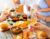Mains avec le vin rouge grillant au-dessus de la table servie avec la nourriture Photographie stock libre de droits