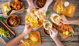 Mains avec le vin rouge grillant au-dessus de la table servie avec la nourriture Photo libre de droits