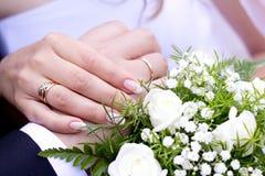 Mains avec les boucles de mariage et le bouquet de mariage Images stock