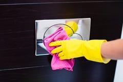 Mains avec les gants protecteurs en caoutchouc jaunes nettoyant le bouton affleurant de toilette Photos libres de droits