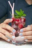Mains avec les ongles manucurés courts colorés avec le vernis à ongles gris photo libre de droits