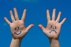 Mains avec les sourires et le modèle de tristesse photos libres de droits