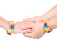mains avec un bracelet modelé comme drapeau d'arc-en-ciel D'isolement sur le blanc Image libre de droits