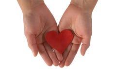 Mains avec un coeur rouge Image stock