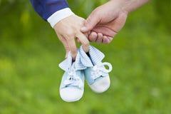 Mains bleu-clair minuscules de booteesin de maman et de papa Image libre de droits