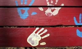 Mains bleues et blanches sur le rouge Images stock