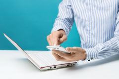 Mains, carnet et Smart-téléphones masculins pour des affaires dans le bureau sur le fond bleu Photographie stock